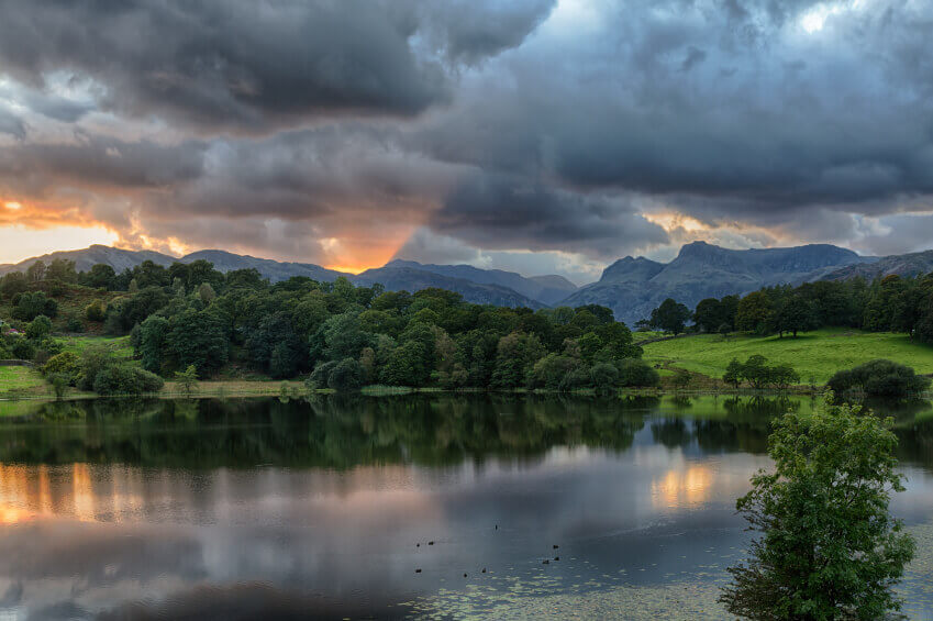 Photo of sunset behind mountain range in the Lake District.